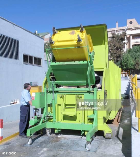 Operator tipping waste from trash bin into rubbish compactor at Clinica Hospital Malaga Malaga Province Spain
