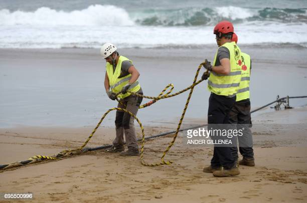 Operators handle an undersea fiber optic cable at Arrietara beach near the Spanish Basque village of Sopelana on June 13 2017 Facebook and Microsoft...