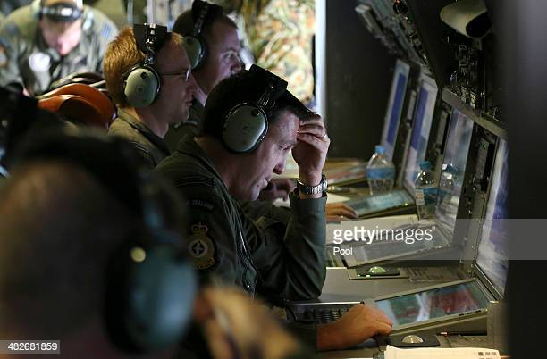 Operators monitor TAC stations onboard a RNZAF P3 Orion during search operations for wreckage and debris of missing Malaysia Airlines Flight MH370 in...