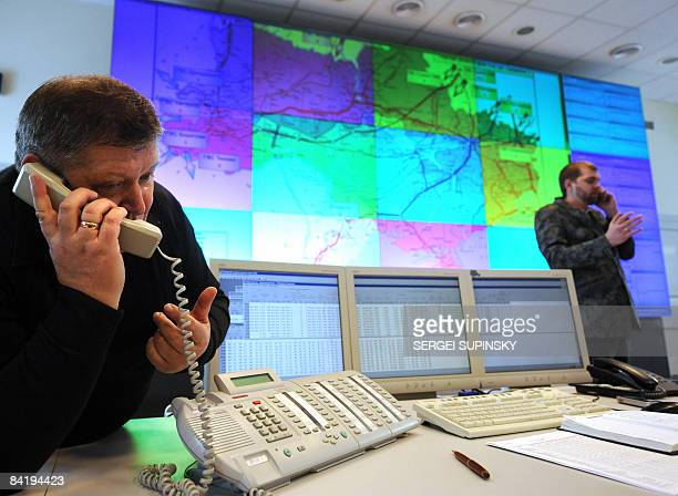 Operators speak on their phones in front of a screen displaying gas pipelines on Ukraine's territory at a main control point of the Ukrgastrans...