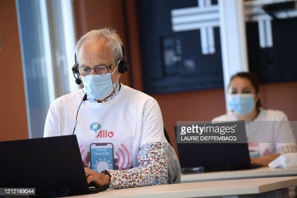 Operators wearing a protective facemask work in a call centre for 'contact tracing' where phonecalls are made to map how many people in Brussels have...