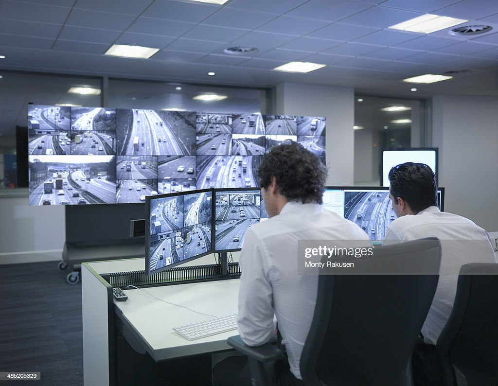 Operators with screens in traffic control room : Stock Photo