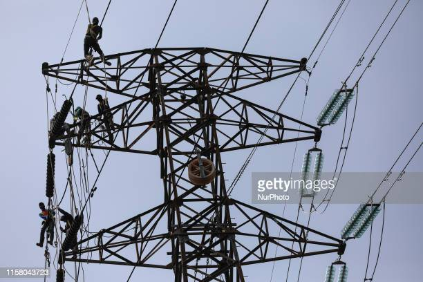 Operators work on a high voltage tower in Jakarta Indonesia July 27 2019