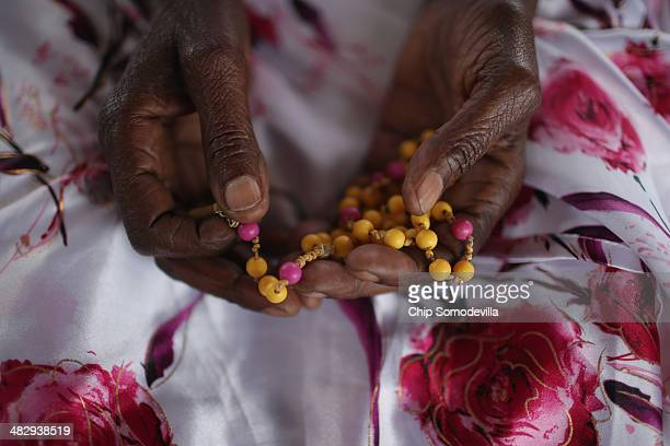 Ophelia Nyiramagumeri holds a rosary given to her by her nephew who was killed in the 1994 genocide while gathering with thousands of others at the...