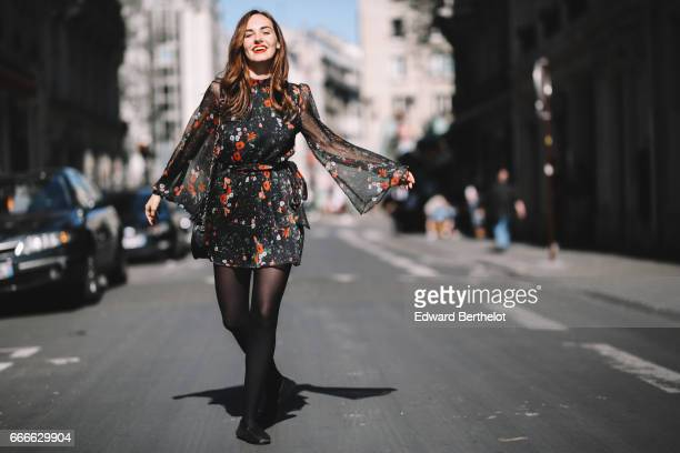 Ophelie Duvillard fashion blogger and model wears Bobbies shoes a Mango floral print dress and a Mango bag on April 9 2017 in Paris France