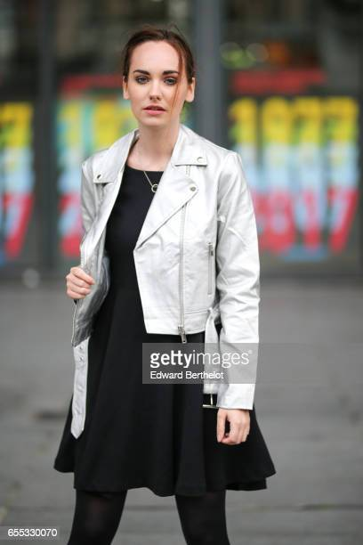 Ophelie Duvillard model and fashion blogger wears a silver jacket a black lace dress a black leather bag black tights and black leather shoes on...