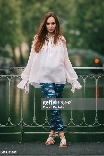 Ophelie Duvillard model and fashion blogger wears Asos white sandals Seafarer blue pants with prints and a Redemption white lace top at Canal Saint...