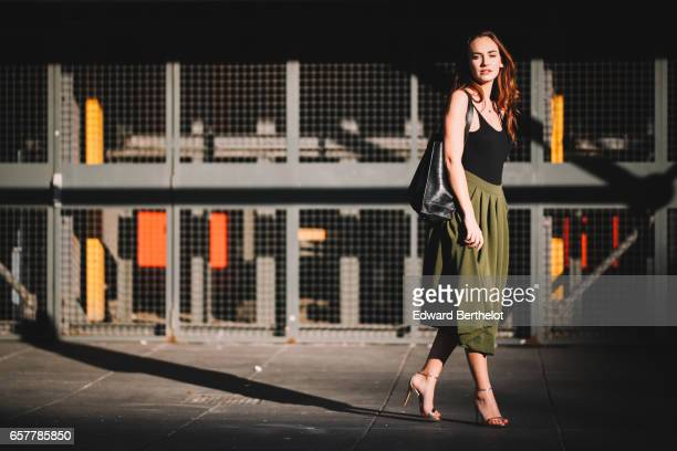 Ophelie Duvillard model and fashion blogger wears Steve Madden heels shoes a Louche green skirt an Urban Outfitters black low neck sleeveless shirt a...