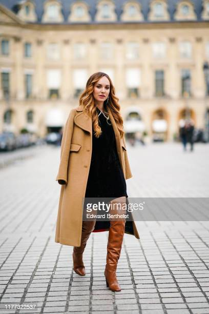 Ophelie Duvillard wears earrings a black mini dress with a bejeweled collar a camel wool coat tancolor thigh high boots outside Guy Laroche during...