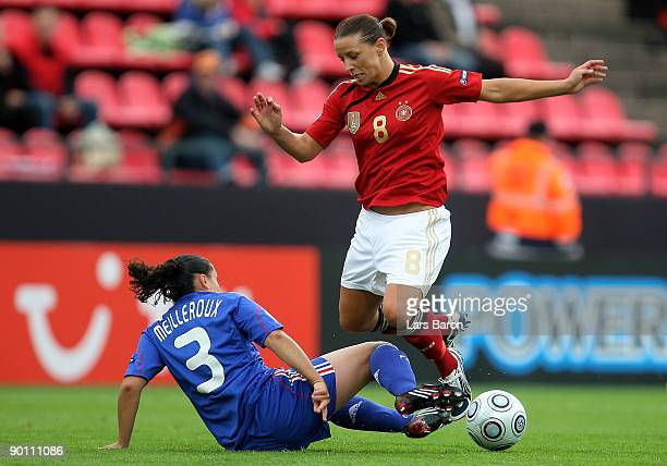 Ophelie Meilleroux of France challenges Inka Grings of Gemrany during the UEFA Women's Euro 2009 group B preliminary match between France and Germany...