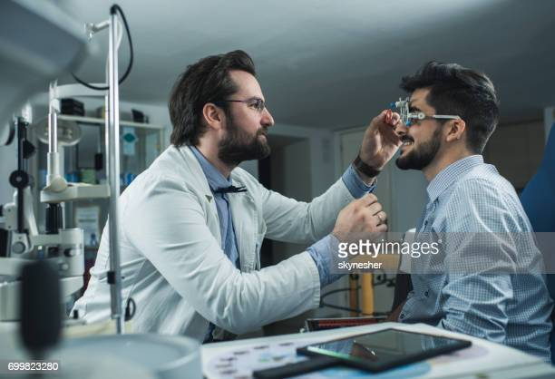 Ophthalmologist doing an eyesight exam of a young man with trial frame.