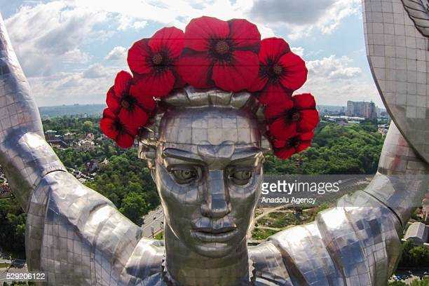 Opium poppy crown is placed on the Statue 'Mother Motherland' in Kiev Ukraine on May 8 2016