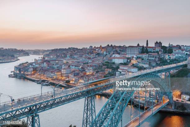 oporto, skyline and cityscape at sunset, louis i bridge on douro river illuminated. - porto portugal stock pictures, royalty-free photos & images