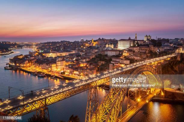 oporto, skyline and cityscape at sunset, louis i bridge on douro river illuminated. - oporto portogallo foto e immagini stock
