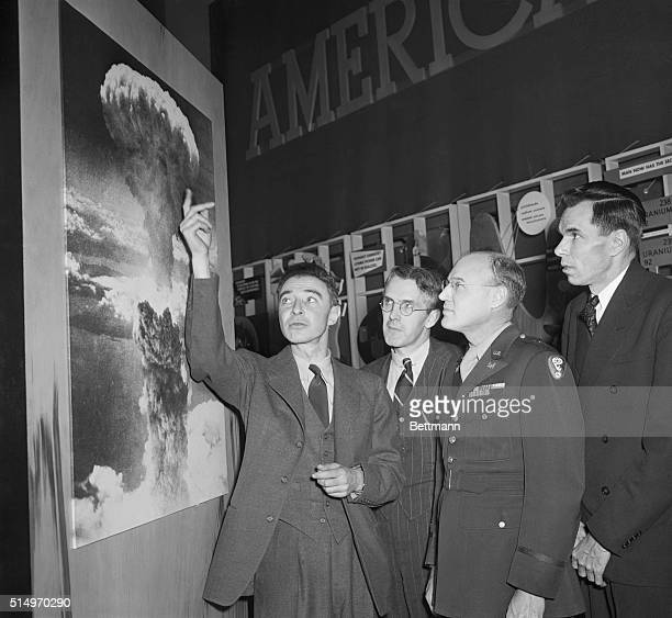 RJ Oppenheimer who was in charge of the Los Alamos New Mexico atomic bomb experiment points to a photograph of the huge column of smoke and flame...