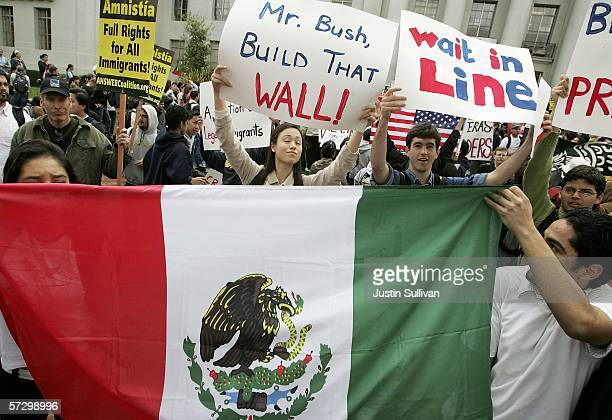 Opponents of House bill HR4437 display a Mexican flag in front of proponents' signs during a rally for immigration rights on the campus of the...