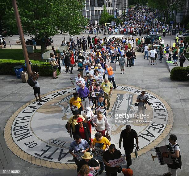 Opponents of North Carolina's HB2 walk over the state seal as they enter the legislative building for a sitin protest in Raleigh NC on Monday April...