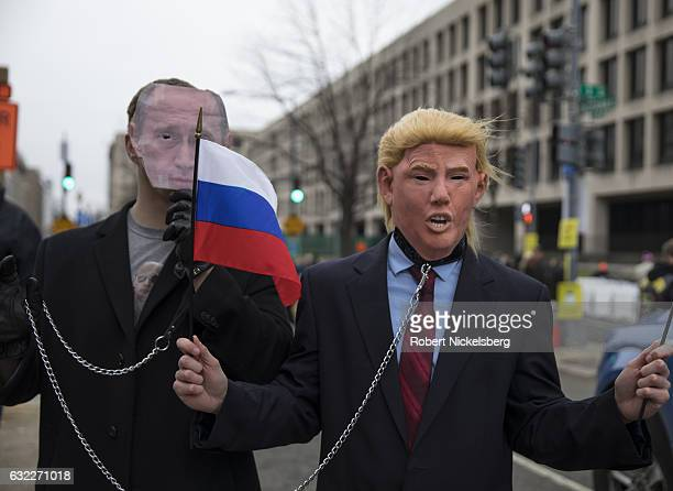 Opponents of President Donald J Trump and President Vladimir Putin wear masks and chains after the inauguration ceremony January 20 2017 in...