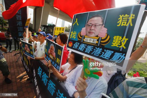 Opponents of the socalled Umbrella Nine democracy activists hold placards outside a district court ahead of their verdicts being delivered in Hong...