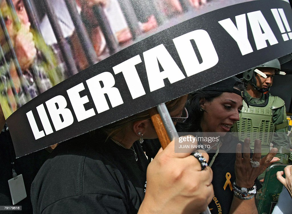 Opponents of Venezuelan president Hugo Chavez hold a sign reading 'Freedom Now!!' during a demonstration 23 January, 2008 in Caracas. The Venezuelan government commemorated today the 50th anniversary of the fall of the last dictatorship -gen. Marcos Perez Jimenez (1948-58). AFP PHOTO/Juan BARRETO