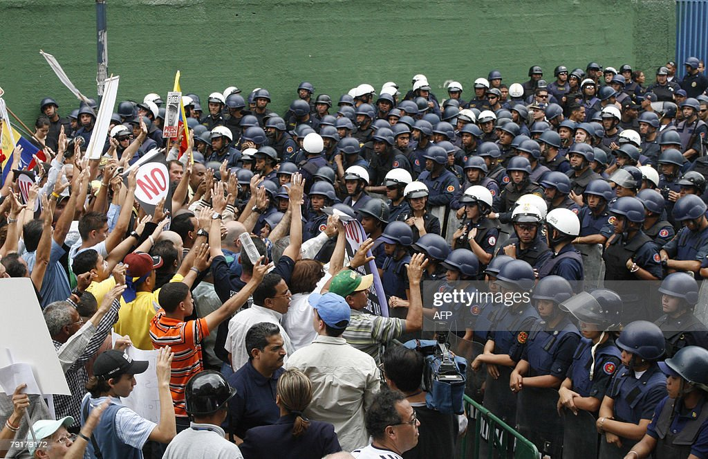 Opponents of Venezuelan president Hugo Chavez shout slogans in front of a riot police block during a demonstration 23 January, 2008 in Caracas. The Venezuelan government commemorated today the 50th anniversary of the fall of the last dictatorship -gen. Marcos P?rez Jim?nez (1948-58). AFP PHOTO/Enrique HERNANDEZ