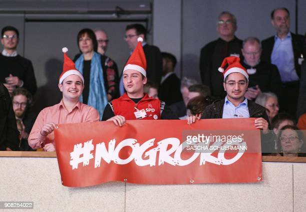 "Opponents to a a new grand coalition unfold a banner reading ""#NoGroKo"" on January 21, 2018 in Bonn, western Germany, at the beginning of the Social..."