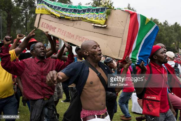 Opponents to South African President Jacob Zuma use a fake coffin to signify his end outside the Union Buildings in Pretoria. South African political...