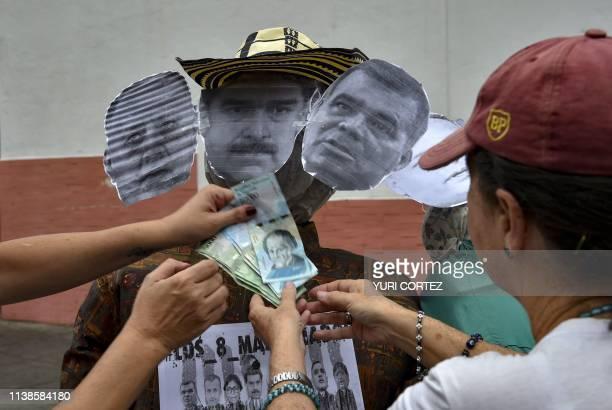 Opponents to the government place Bolivar banknotes on dummies depicting Venezuelan President Nicolas Maduro , Venezuelan Defense Minister Vladimir...