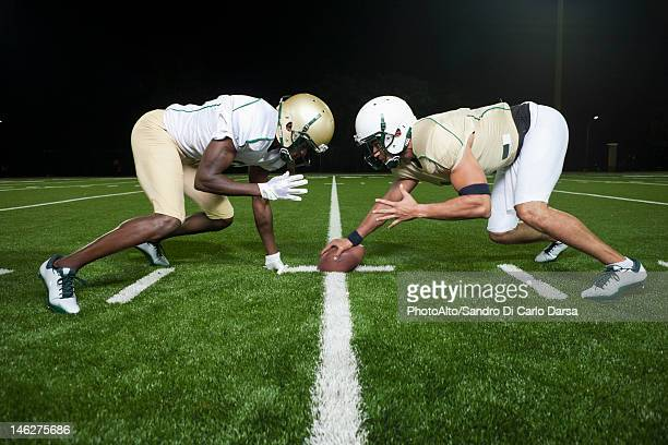 opposing football players crouched at line of scrimmage - angesicht zu angesicht stock-fotos und bilder
