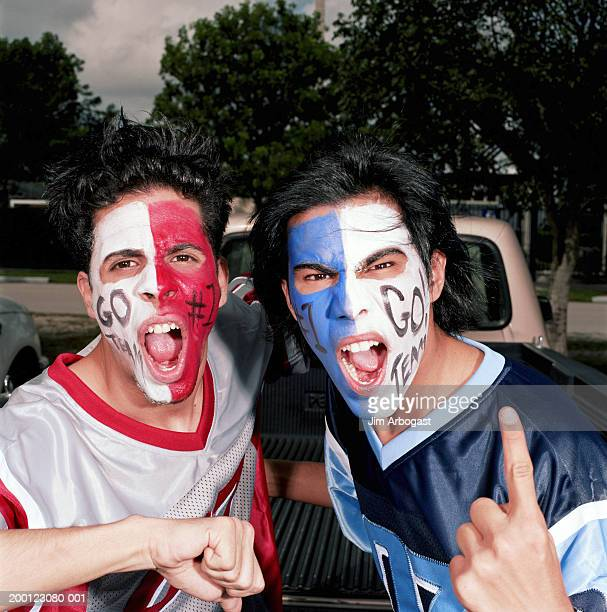 Opposing male sports fans wearing face paint, cheering, portrait