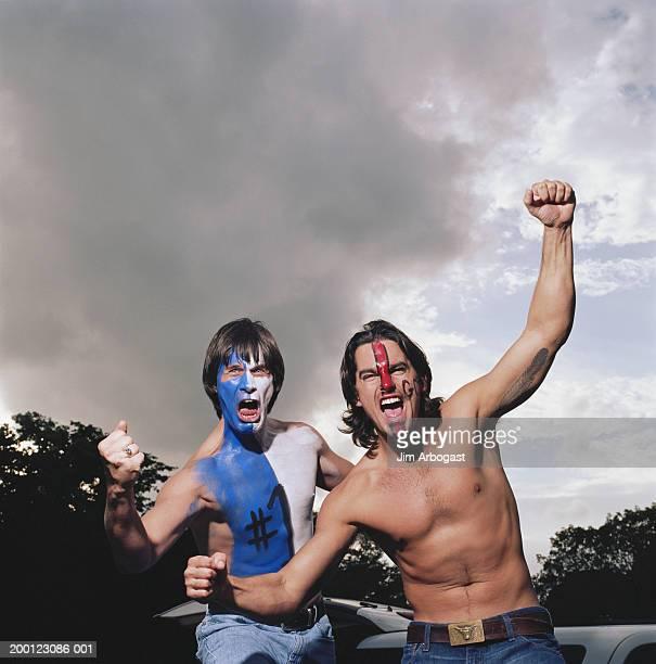 Opposing sports fans wearing face paint, cheering, portrait