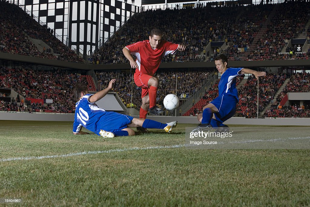 Opposite players tackling footballer : Stock Photo