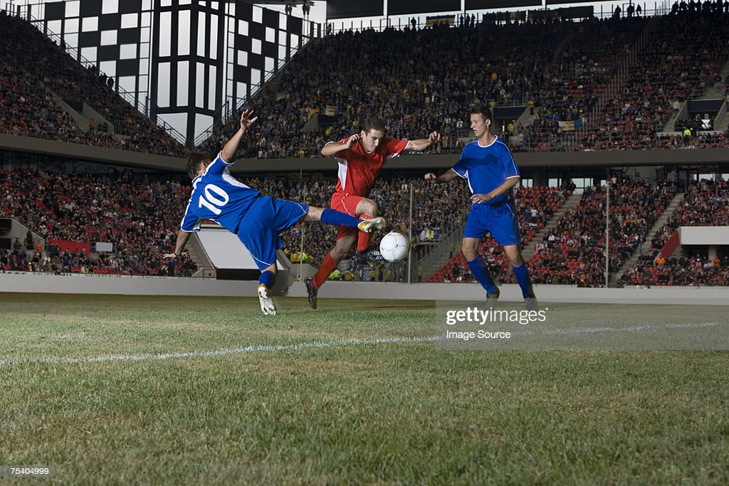 Abordar footballer frente a los jugadores : Foto de stock