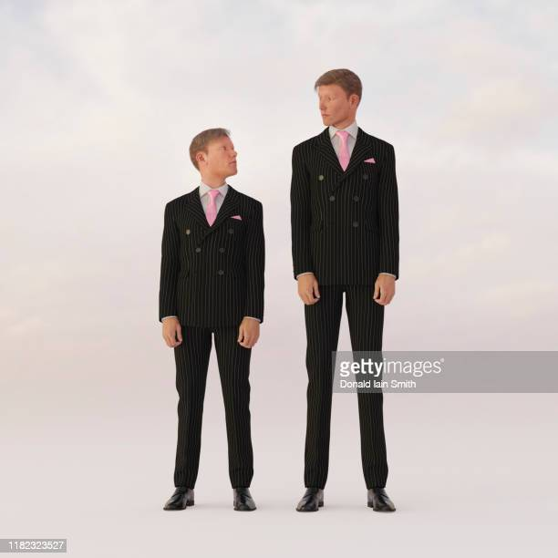 opposites: tall and short businessmen looking at each other - tall person stock pictures, royalty-free photos & images