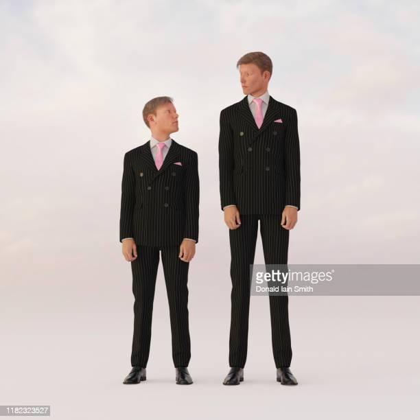 opposites: tall and short businessmen looking at each other - lang lengte stockfoto's en -beelden