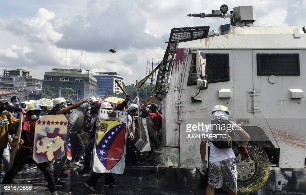 Opposition activists and riot police clash during a protest against President Nicolas Maduro in Caracas on May 10 2017 Venezuelan protesters hit the...