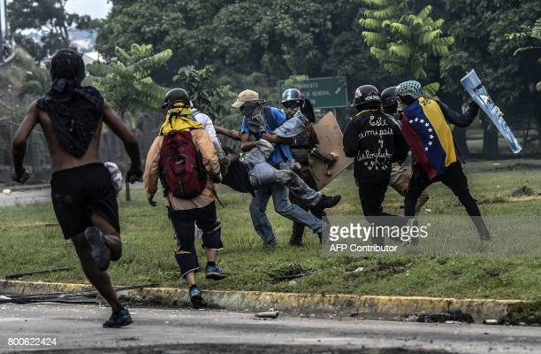 TOPSHOT Opposition activists assist an injured protester in clashes with police during a demonstration against the government of Venezuelan President...