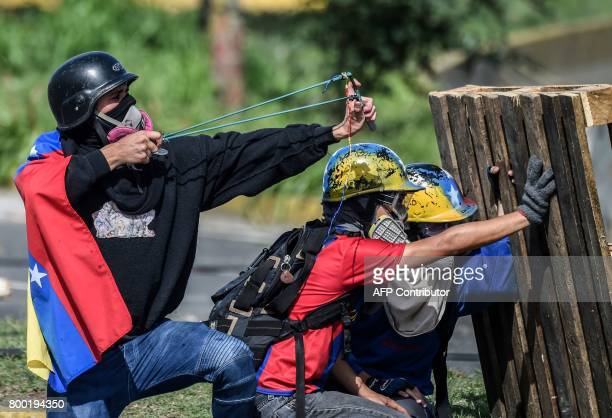 Opposition activists blocking a highway in Caracas clash with police during a protest against the government of President Nicolas Maduro on June 23...