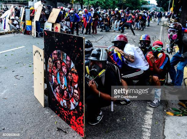 Opposition activists hide behind shields as they clash with the p[olice during a march towards the Supreme Court of Justice in an offensive against...