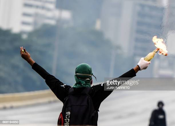 TOPSHOT Opposition activists protesting against the government of Nicolas Maduro clash with riot police in Caracas on April 13 2017 A 32yearold man...