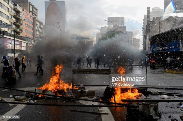 TOPSHOT Opposition activists protesting against the newly inaugurated Constituent Assembly and riot police clash in Caracas on August 4 2017...