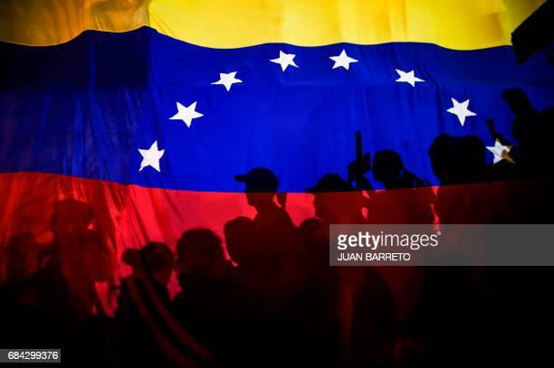 TOPSHOT Opposition activists seen here behind a Venezuelan flag protest against the deaths of 43 people in clashes with the police during weeks of...