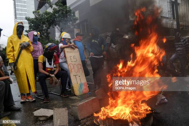Opposition activists wearing gas mask and other face protection to protect themselve against the smoke are seen burning a tire front of the riot...
