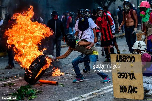 TOPSHOT Opposition demonstrators burn a tire during an antigovernment protest in Caracas on July 26 2017 Venezuelans blocked off deserted streets...