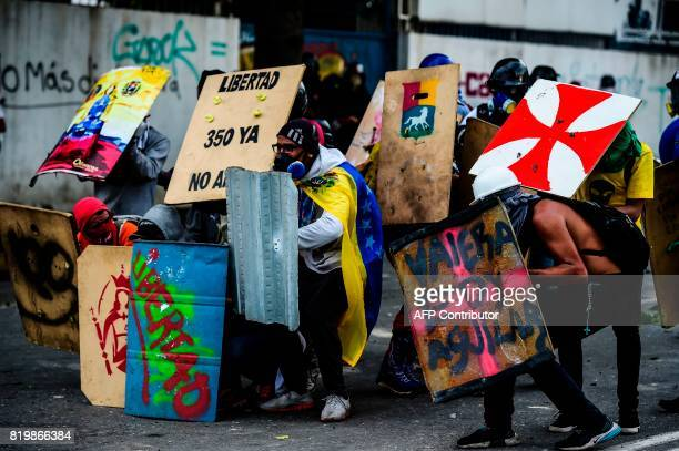 TOPSHOT Opposition demonstrators clash with riot police during an antigovernment protest in Caracas on July 20 2017 A 24hour nationwide strike got...