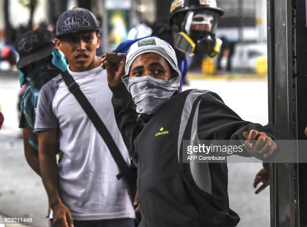 Opposition demonstrators clash with riot police ensuing an antigovernment protest in Caracas on July 26 2017 Venezuelans blocked off deserted streets...