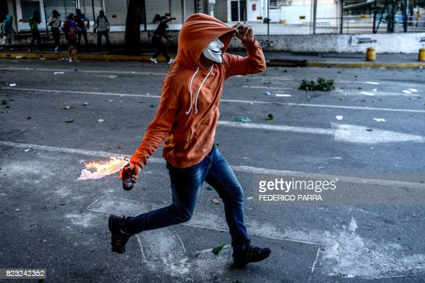 TOPSHOT Opposition demonstrators clash with riot police ensuing an antigovernment protest in Caracas on July 26 2017 Venezuelans blocked off deserted...