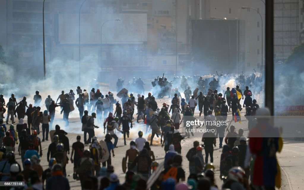 TOPSHOT - Opposition demonstrators clash with riot police in Caracas, on May 26, 2017. Riot police in Venezuela fired tear gas and water cannon to stop anti-government protesters from marching on a key military installation Friday during the latest violence in nearly two months of unrest. /