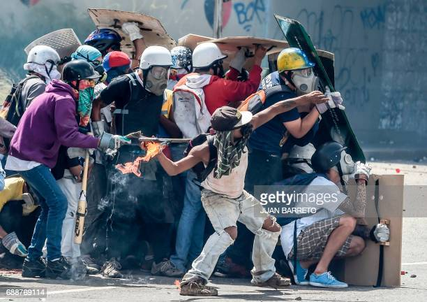 TOPSHOT Opposition demonstrators equipped with protective hardhats gloves and gas masks take cover behind homemade shields as they clash with riot...
