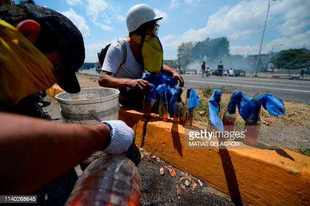 Opposition demonstrators prepare Molotov cocktails during clashes with soldiers loyal to Venezuelan President Nicolas Maduro after troops joined...
